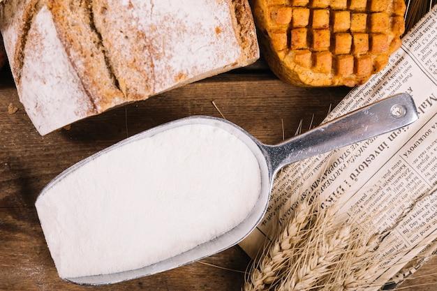 Vista superior de farinha na pá com pão assado na mesa de madeira