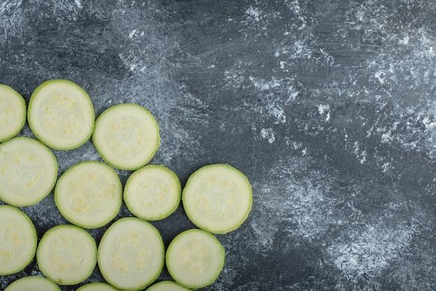 Vista superior de fatias de abobrinha frescas em fundo cinza.