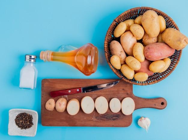 Vista superior de fatias de batata e faca na tábua com os inteiros na cesta manteiga sal e pimenta preta e alho na superfície azul