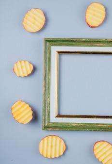 Vista superior de fatias de batata em torno do quadro na superfície azul com espaço de cópia