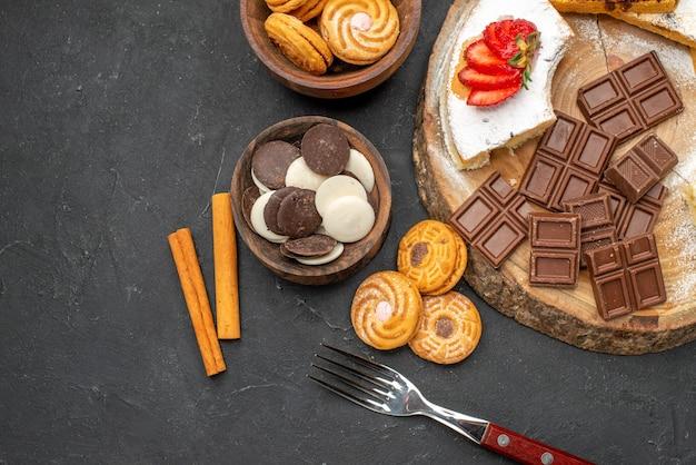 Vista superior de fatias de bolo com biscoitos e chocolate em fundo escuro
