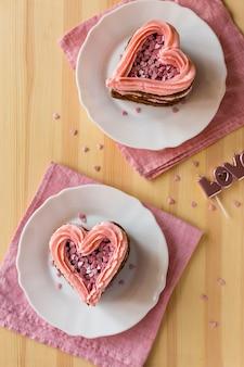 Vista superior de fatias de bolo em forma de coração com fundo de madeira
