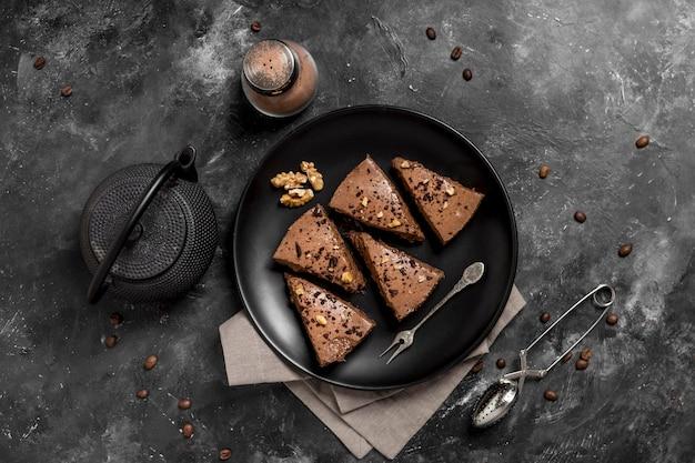 Vista superior de fatias de bolo no prato com bule de chá e grãos de café