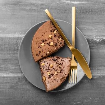 Vista superior de fatias de bolo no prato com talheres de ouro