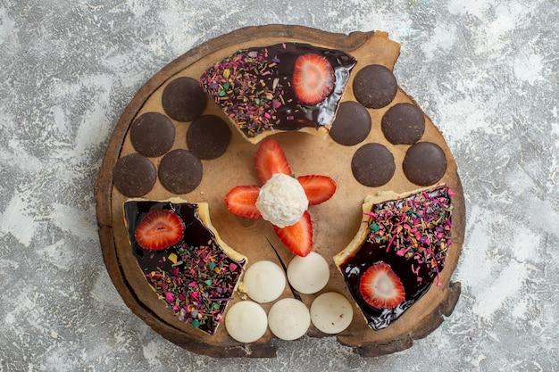 Vista superior de fatias de bolo saborosas com biscoitos de chocolate na superfície branca