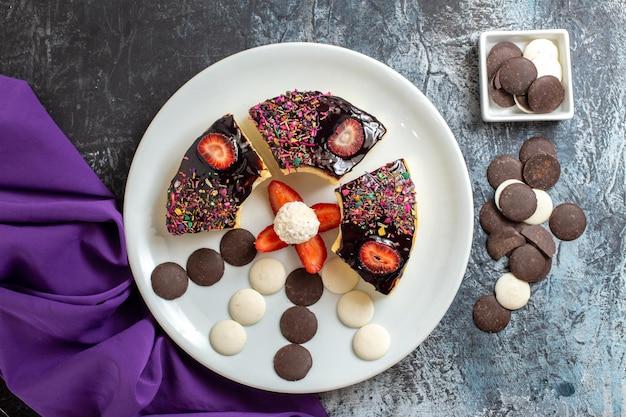 Vista superior de fatias de bolo saborosas com biscoitos de chocolate na superfície escura