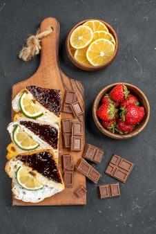 Vista superior de fatias de bolo saborosas com chocolate e frutas na superfície escura