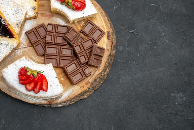 Vista superior de fatias de bolo saborosas com morangos e barras de chocolate na superfície escura