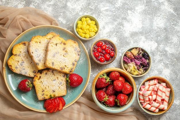 Vista superior de fatias de bolo saborosas com morangos frescos na luz