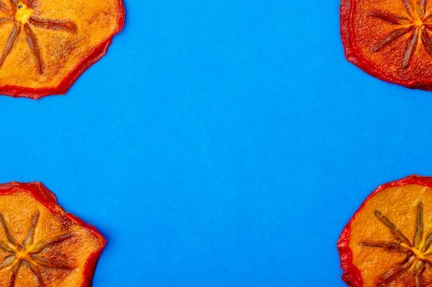 Vista superior de fatias de caqui secas isoladas sobre fundo azul, com espaço de cópia