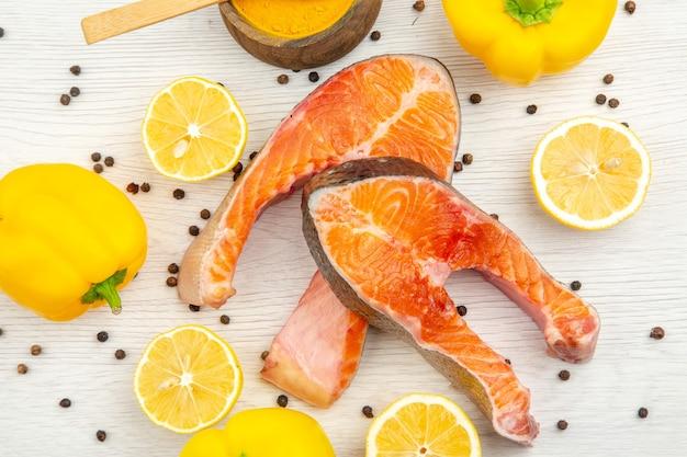 Vista superior de fatias de carne fresca com rodelas de limão e pimentão no fundo branco