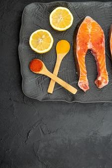 Vista superior de fatias de carne fresca dentro do prato com rodelas de limão em fundo escuro