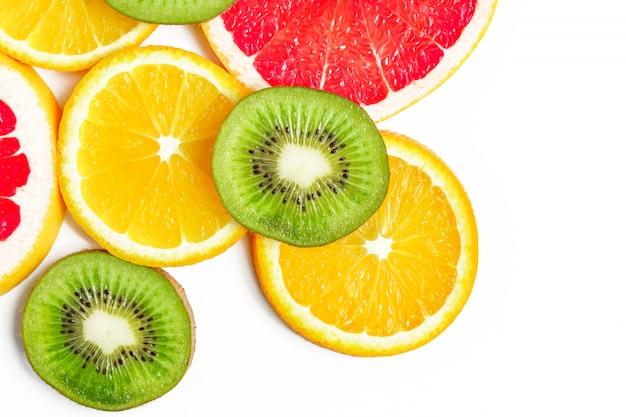 Vista superior de fatias de citrinos - kiwi, laranjas e toranjas isoladas com espaço de cópia.