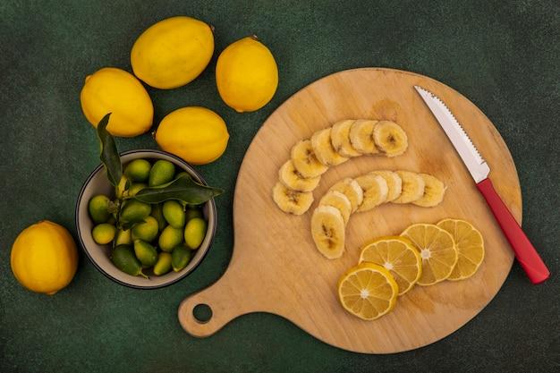Vista superior de fatias de frutas frescas, como bananas e limões em uma placa de cozinha de madeira com uma faca com kinkans em uma tigela com limões isolados em um fundo verde