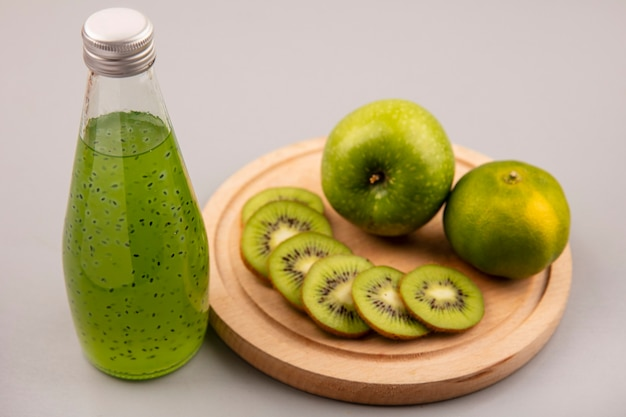 Vista superior de fatias de kiwi fresco picado em uma placa de cozinha de madeira com maçã verde e tangerina com suco de kiwi fresco em uma garrafa de vidro