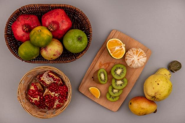 Vista superior de fatias de kiwi fresco picado em uma placa de cozinha de madeira com tangerinas e romãs em um balde com pêra e marmelo isolado