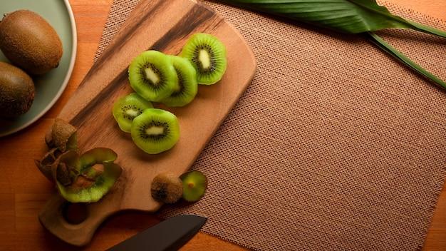Vista superior de fatias de kiwi verde na bandeja de madeira na mesa de jantar com espaço de cópia
