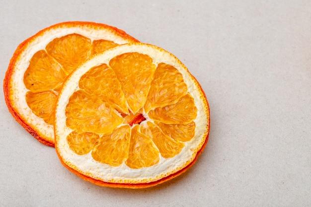 Vista superior de fatias de laranja secas, dispostas em fundo branco, com espaço de cópia