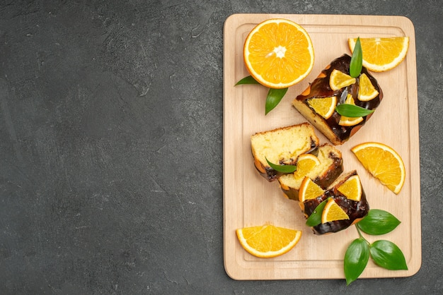 Vista superior de fatias de limão fresco e fatias de bolo picadas no lado esquerdo do fundo escuro