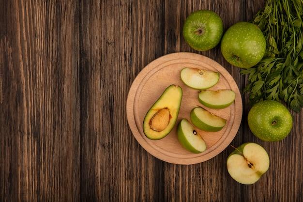 Vista superior de fatias de maçã fresca em uma placa de cozinha de madeira com metade do abacate com maçãs e salsa em uma superfície de madeira com espaço de cópia