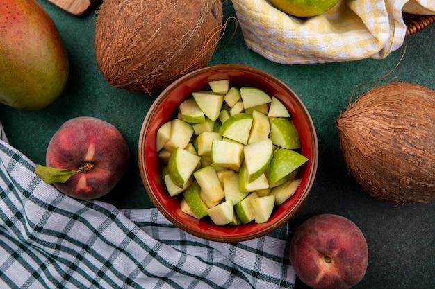 Vista superior de fatias de maçã picada em uma tigela vermelha com coco pêssegos em chekcked e verde