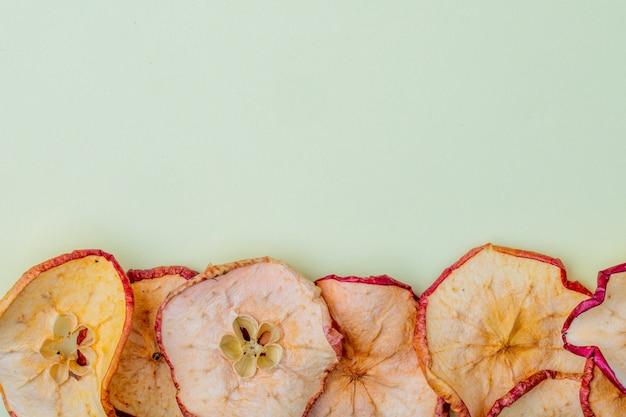 Vista superior de fatias de maçã seca, isoladas sobre fundo azul claro, com espaço de cópia