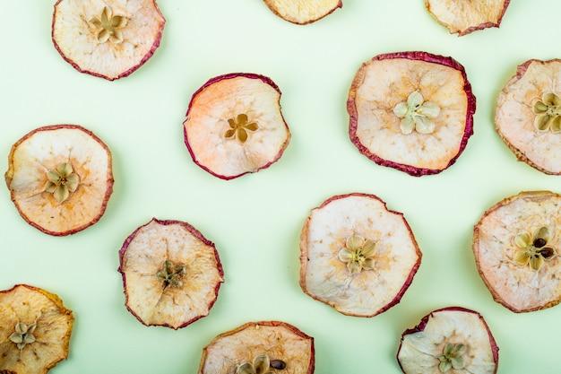 Vista superior de fatias de maçã seca isoladas sobre fundo azul claro