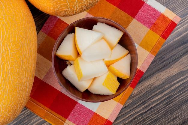 Vista superior de fatias de melão em uma tigela no pano xadrez com os inteiros sobre fundo de madeira