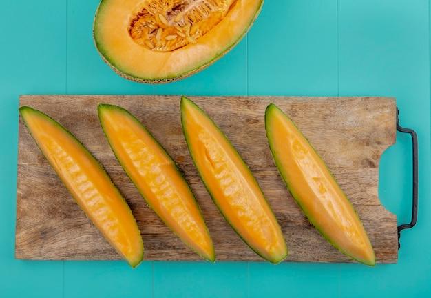 Vista superior de fatias de melão frescas e saudáveis em uma placa de cozinha de madeira com superfície azul