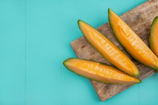 Vista superior de fatias de melão melão deliciosas e frescas na placa de cozinha de madeira em azul