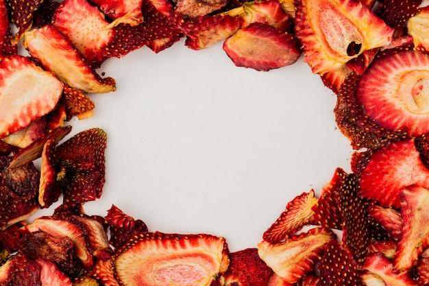 Vista superior de fatias de morango secas, dispostas em fundo branco, com espaço de cópia