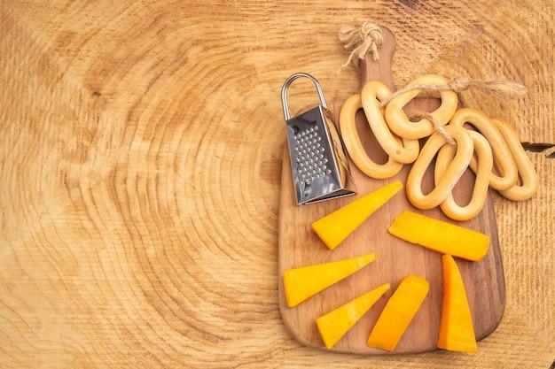 Vista superior de fatias de pãezinhos ovais ralador de caixa de queijo em uma tábua em um terreno de madeira com espaço para cópia
