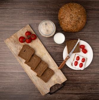 Vista superior de fatias de pão de centeio e tomates na tábua com leite de espiga e flocos de aveia em fundo de madeira