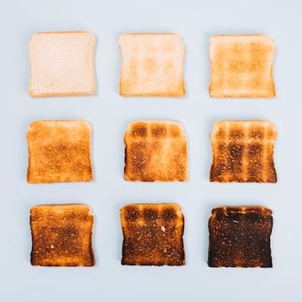 Vista superior de fatias de pão em diferentes estágios de brindar em fundo branco