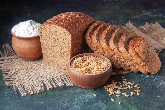 Vista superior de fatias de pão preto de farinha em uma tigela e trigo em uma toalha de cor nude sobre fundo de cor marrom