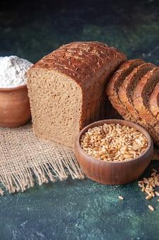 Vista superior de fatias de pão preto de farinha em uma tigela e trigo em uma toalha de cor nude sobre fundo de cor verde escuro