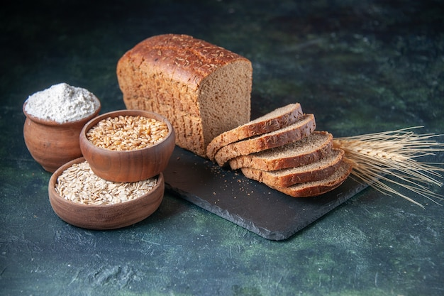 Vista superior de fatias de pão preto, farinha de trigo sarraceno de aveia no quadro de cor escura sobre fundo azul envelhecido
