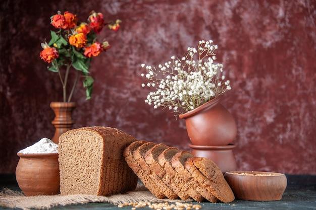 Vista superior de fatias de pão preto, farinha em uma tigela e trigo em uma toalha de cor nude e vasos de flores em um fundo de cores mistas