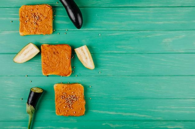 Vista superior de fatias de pão quadrado, rebocadas com caviar de berinjela, coberto com grãos de pimenta, sobre fundo verde de madeira, com espaço de cópia