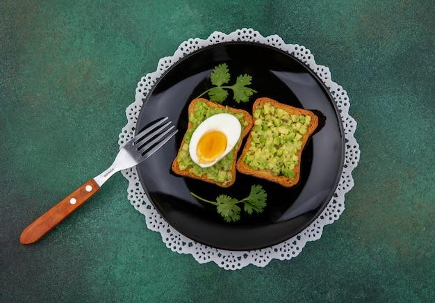 Vista superior de fatias de pão torradas com polpas de abacate e ovo em uma tigela com garfo na superfície verde