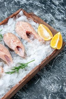 Vista superior de fatias de peixe cru com fatias de limão e gelo na tábua de madeira na mesa