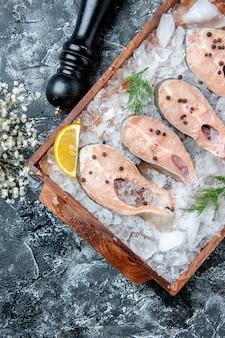 Vista superior de fatias de peixe cru com gelo em um moedor de pimenta em tábua de madeira