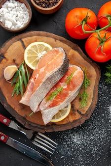 Vista superior de fatias de peixe fresco com rodelas de limão e tomate na mesa escura
