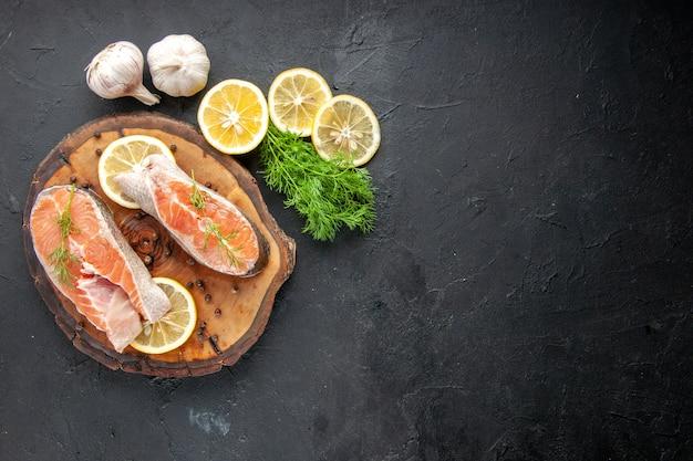 Vista superior de fatias de peixe fresco com rodelas de limão na mesa escura
