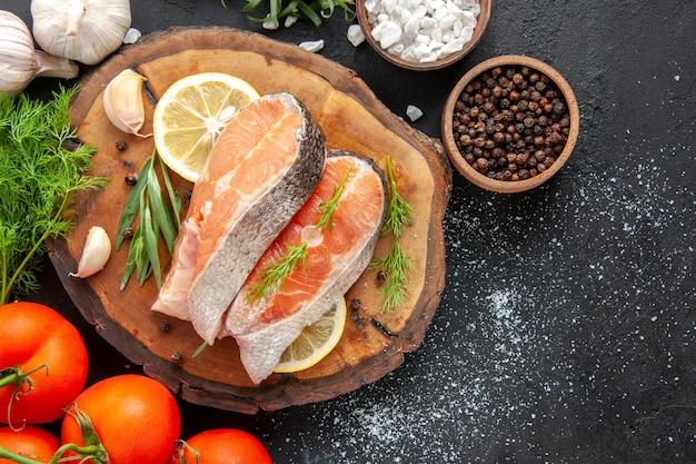 Vista superior de fatias de peixe fresco com tomate e rodelas de limão na mesa escura