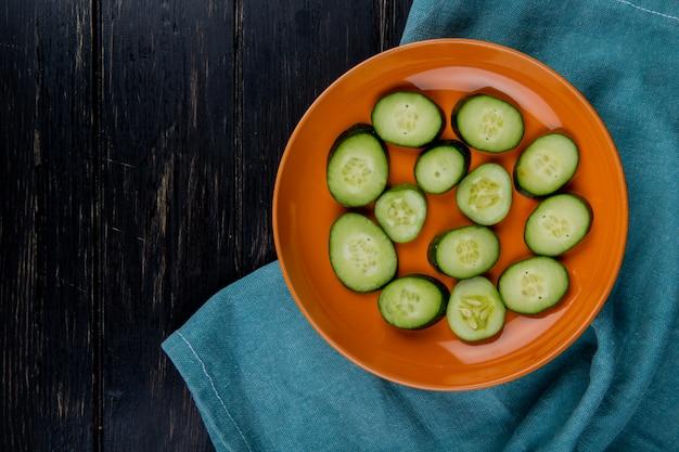 Vista superior de fatias de pepino em prato no pano azul e superfície de madeira com espaço de cópia