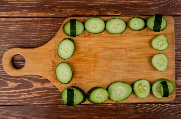 Vista superior de fatias de pepino na tábua e superfície de madeira