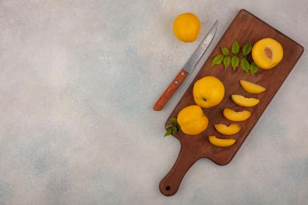 Vista superior de fatias de pêssegos amarelos frescos em uma placa de cozinha de madeira com uma faca em um fundo branco com espaço de cópia