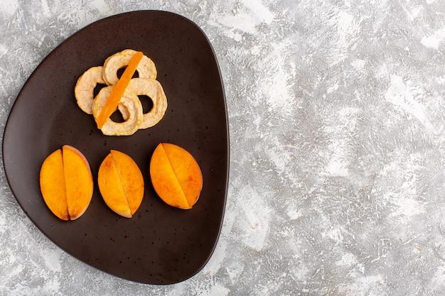 Vista superior de fatias de pêssegos frescos dentro do prato com anéis de abacaxi na superfície branca clara