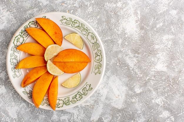 Vista superior de fatias de pêssegos frescos dentro do prato com limões na superfície branca clara